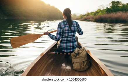 Paddling the wooden canoe. Rear view of travel girl canoeing on the sunset lake. Kayaking, canoeing, outdoors