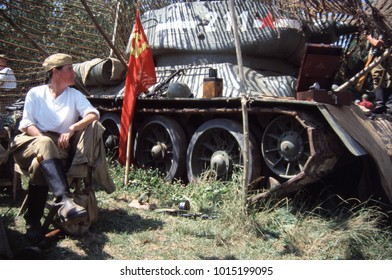 Paddock Wood Kent England 2003. A female reenactor dressed in WW2 Russian uniform sits next to her T34 tank during a re-enactment of WW2.