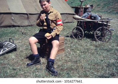 Paddock Wood Kent England 2003. A young reenactor of WW2 wears the uniform of a member of the Hitler Youth while eating some bread in a camp scene with German equipment in the background.