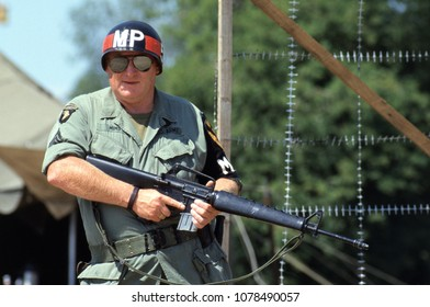 Paddock Wood Kent England 2003. An unidentified reenactor of the Vietnam War wears the period uniform of a US Military Policeman he stands guard holding an M16 rifle at a re-enactment event.