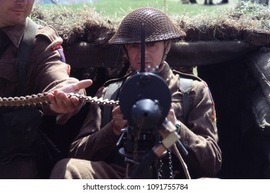 Paddock Wood Kent UK 2003. An unidentified reenactor of WW2 wears the period uniform of a British Infantryman he sits with his loader behind a WW2 Vickers Machine Gun.