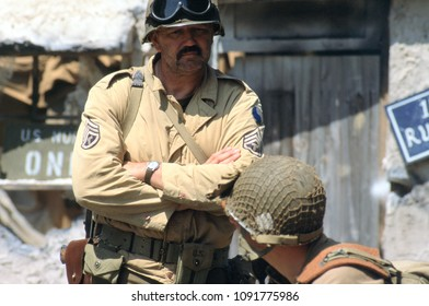 Paddock Wood Kent UK 2003. An unidentified reenactor of WW2 stands talking in conversation wearing the period uniform of a US Sargent of the Tank Corp at a reenactment of the Battle of Falaise 1944.