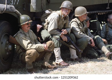 Paddock Wood Kent UK July 2003. WW2 Reenactors wear the period uniform of US Paratroopers they sit against a truck relaxing at a re-enactment event.