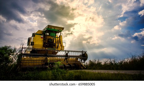 Paddy crop cutting machine over dramatic sunset dark sky