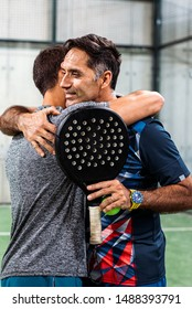 padel players embracing after win a padel match in a green grass padel court indoor