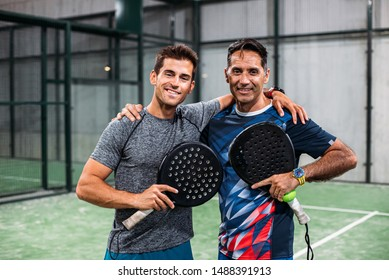 padel players looking at camera and embracing after win a padel match in a green grass padel court indoor