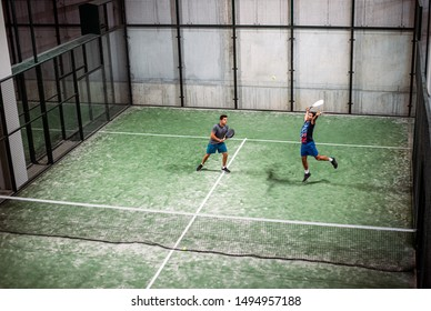 padel players playing padel in a green grass padel court indoor