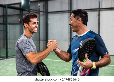 padel players playing padel and shaking hands after win a padel match in a green grass padel court indoor