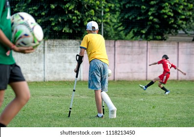 PADERNO DUGNANO, ITALY-JUNE 09, 2018: injured player with crutches on the soccer field during the european soccer children match between Italian and Swedish teams, in Paderno Dugnano, near Milan.