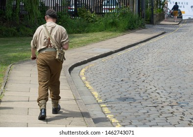 Padiham, Lancashire/UK - June 29th 2019: caucasian man dressed in world war 2 soldier's uniform at a 1940s weekend event walking on the pavement next to a cobbled street