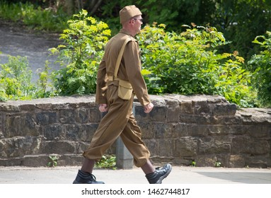 Padiham, Lancashire/UK - June 29th 2019: isolated caucasian man dressed in world war 2 soldier's uniform at a 1940s weekend event walking along street next to a stone wall and greenery