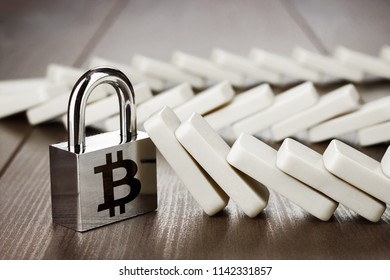 padlock with bitcoin symbol standing still. bitcoin cryptocurrency based on blockchain technology security reliability concept over wooden table