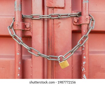 Padlock and chain fastening the door of a red container