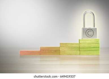 Padlock with Copyright Symbol on Level of Safe Zone Wood Block Wooden Floor and White Background with Copy Space, Security and Protection for copyright concepts.