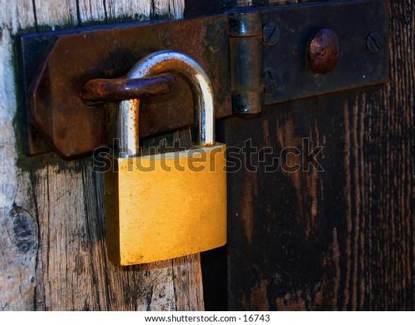 A padlock hanging on a wooden door.