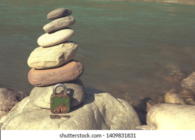 Padlock with a key lies near the cairn. The concept is a closed mind, subconscious and inner world.