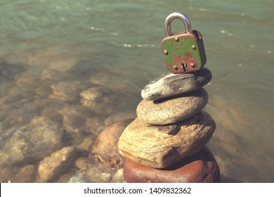 Padlock with key lies on the cairn. The concept is a closed mind, subconscious and inner world.