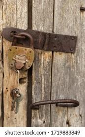 A padlock with keys hangs on an old door. Rustic style, shabby wood, rust on metal.