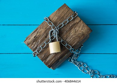 padlock locked wooden treasure box on blue wood background