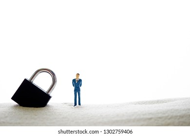 Padlock with miniature man on sand