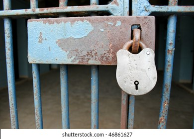 Padlock on the cell door of a prison.  Focus on the padlock with copy space room on the latch.  Dark and gloomy bars and cell in background.  The rust suggests a long stay.