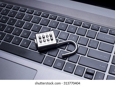 padlock on laptop computer security concept