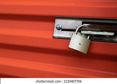 Padlock on an orange self storage unit door.