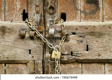 Padlock with rusty chain on wooden door. Locked gate.
