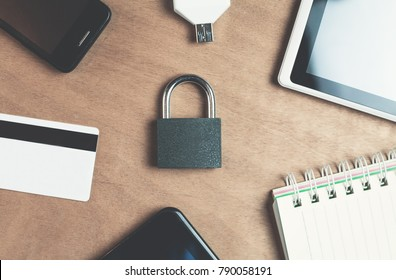 Padlock tablet with phone and credit card on a wood background.