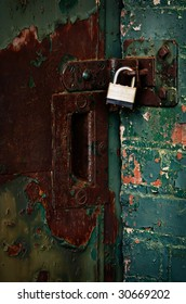 padlocked rusty door in brick wall
