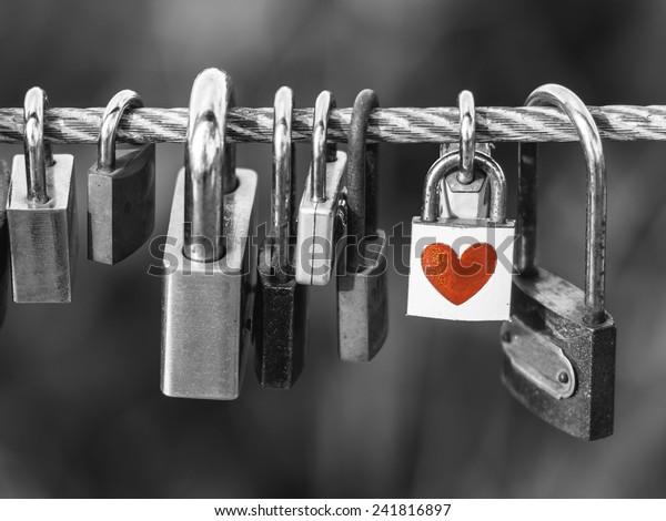 Замки с формой сердца на веревочном мосту на черном и белом фоне, концепция дня Святого Валентина.