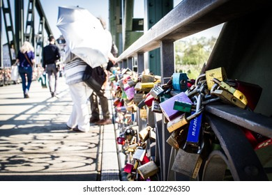 Padlocks on a bridge symbol of eternal love and umbrella in the background