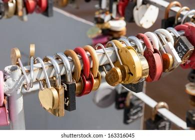 Padlocks, symbols of love hanging on the railing of the bridge