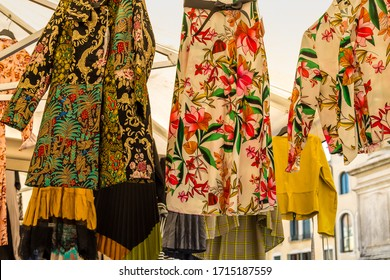 PADOVA, ITALY - FEBRUARY 23, 2019: sunlight is enlightening colorful dresses for sale in market in Padua