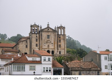 Padron, Spain - 10/20/2018: landmark od Padron in Galicia, Spain. Ancient temple with houses on Camino de Santiago way. Medieval catholic architecture. Travel in Europe.