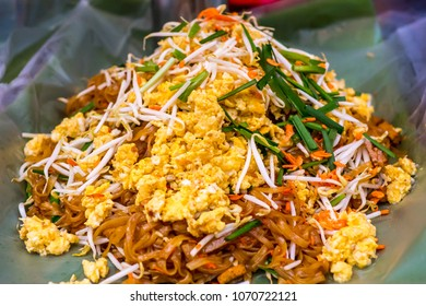padthai - stir fly noodle with orange curry sauce served with banana leaves plate, presented in traditional thai style. Thai name for stir fly noodle is pud mhee. stir fly noodle with shrimp.