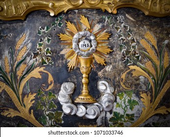 Padua, Italy - April 2, 2018: Detail of an abbey altar painted in gold with depicted the Eucharist chalice.