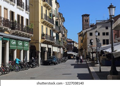 Padua, Italy - September 28, 2018: Shops on Piazza dei Signori square and people walking in the street in Padua, Italy on September 28, 2018