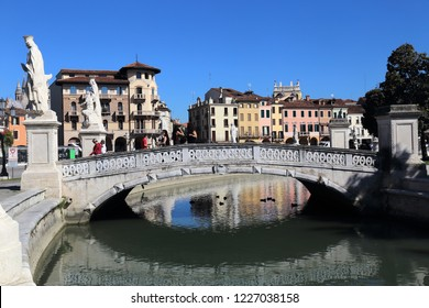 Padua, Italy - September 28, 2018: People standing on a bridge with statues on the Prato della Valle square in Padua, Italy on September 28, 2018