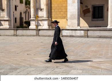 Padua/ Padova, Italy - August 19, 2019:  Roman catholic church cleric priest wearing a black cassock and a galero, flat-brimmed round hat and walking on the street to Duomo di Padova Cathedral.