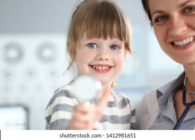Paediatric doctor holding and hugging little cute girl patient portrait