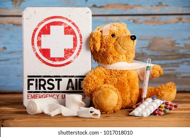 Paediatric First Aid and healthcare concept with a little teddy with its arm in a sling alongside a medical kit with bandages, pills and hypodermic on rustic wood