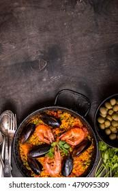 Arrière-plan paella, espace pour texte. La paella dans une poêle noire avec du riz safran, des pois, des crevettes, des moules, des calmars, de la viande. La paella de fruits de mer, plat traditionnel espagnol. Paella sur une table en bois noir rustique. Vue supérieure