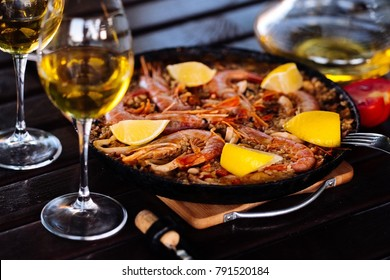 Paella in the pan with the wine on the table. Spanish kitchen. Seafood at home.