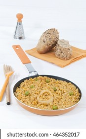 Paella rice, fish and vegetables with bread, Spanish food, pan