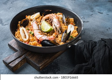 Paella with seafood, prawns, musselsm chicken and rice in pan on grey background