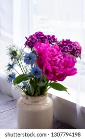 Paeonia officinalis (peony) , Dianthus barbatus (Sweet William),and Nigella damascena (Love in the mist) in a ceramic pot by a window.