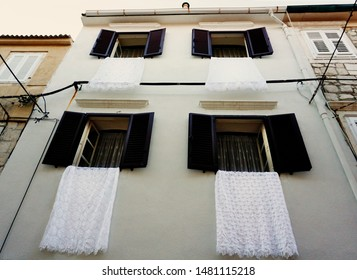 Pag, Croatia, August 15, 2019. Facade of a building in the Croatian town of Pag, decorated with white lace blankets, during the celebration of Saint Mary Day