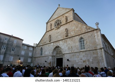 Pag, Croatia, August 15, 2019. A crowd of people stand in front of the church and listen to the Holy Mass. Celebration of Saint Mary Day in the Croatian town of Pag