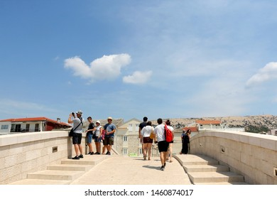 Pag, Croatia - July 7, 2019: Tourists walking on Katine Bridge in town Pag, on island Pag, Croatia. Traditional stone architecture in the background.